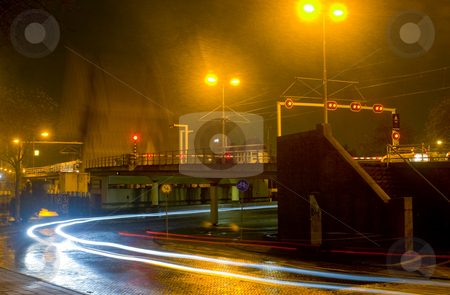 Waiting for a closing bridge during a heavy shower at night stock photo, Cars and a cable car waiting for the bridge to close during a heavy shower on a cold winter night by Corepics VOF