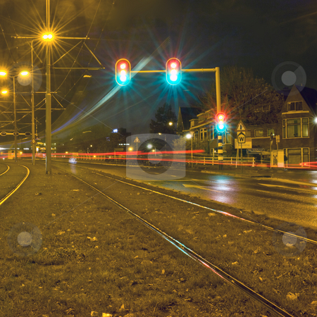 Traffic at night stock photo, A curve in the road with passing cars and the motion blurred lights of a tram, as well as a traffic light jumping from green to red on a rainy night by Corepics VOF