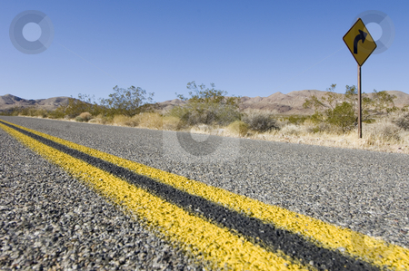 Death Valley Desert road stock photo, A straight desert road in Death valley, with a warning sign of a right bend by Corepics VOF