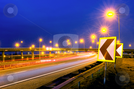 Autobahn Action stock photo, Cars soaring past on a motorway junction, their headlights lighting up the warning signs on the shoulder. by Corepics VOF