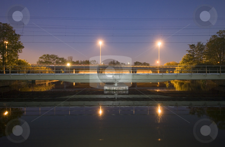 Railway bridge at night stock photo, A railway bridge over a flowing stream at night; with a motorway bridge behind it by Corepics VOF