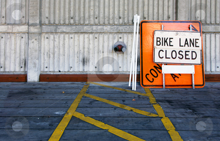 Bike lane closed stock photo, A construction sign with a few poles on a wooden floor, leaning against a weather-beaten wooden fence by Corepics VOF