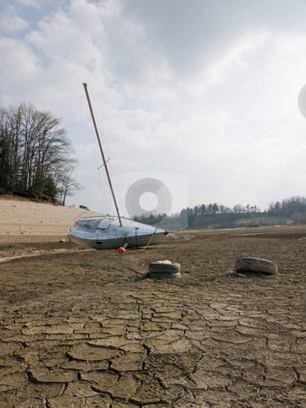 Global warming stock photo, Effect of global warming: a boat on the bottom of a dry lakebed. Dried, cracked earth is the consequence of the climate change and global warming. by FEL Yannick