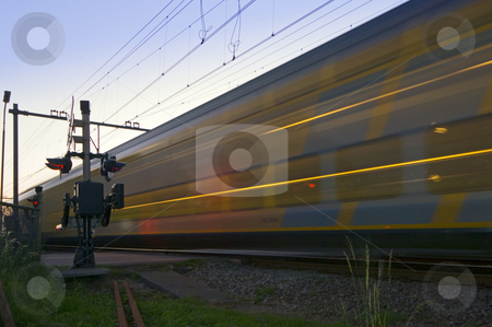 A train Passing at high speed stock photo, A train passing a railroad intersection at high speed by Corepics VOF