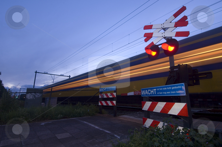 Racing train stock photo, A train racing past a pedestrian crossing just after dusk by Corepics VOF