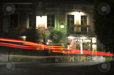 Bar-Restaurant stock photo, A small and cosy bar in an old village, with cars driving past over the cobblestone street at night by Corepics VOF