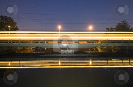 Intercity on railway bridge stock photo, An intercity racing over a railway bridge at night by Corepics VOF