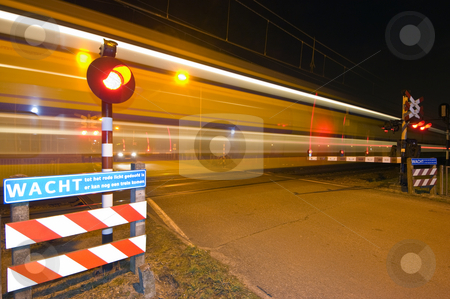 Intercity stock photo, An intercity passing a railroad crossing at night by Corepics VOF