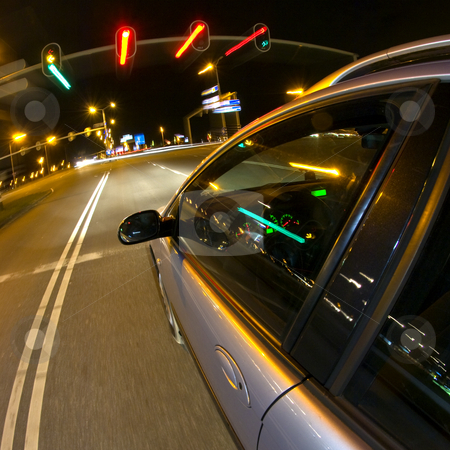Stopping at the traffic lights stock photo, A car, reaching stand-still for the red lights of a traffic light at night by Corepics VOF