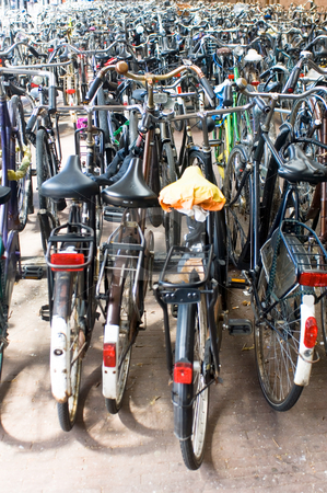 Bicycle parking at the railway station stock photo, A sea of parked bikes at the railway station, the typical way of commuting in the Netherlands Shallow Depth of Field by Corepics VOF