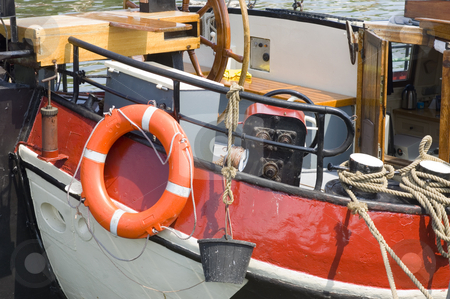 Old ships' details stock photo, Details of the stern of an old flatbottom boat, with a buoy, bucket, anchor winch, ridder, pump and ropes by Corepics VOF