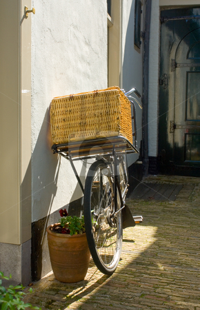 Old Bike stock photo, An old bike with a basket on the handle bar leaning against a plastered wall by Corepics VOF