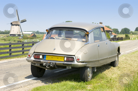 Dutch scene with a French Classic Car stock photo, A vintage 1973 Citroen DS parked on a country road with a windmill in the distance on a bright summer day. by Corepics VOF
