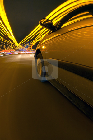 Drivin towards the lights stock photo, A car heading into a commercial zone at night with the bright lights of the city in front. by Corepics VOF