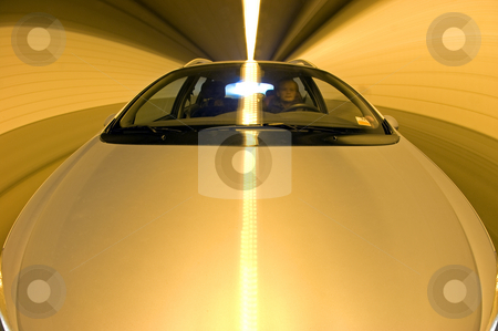 Driving in a Tunnel stock photo, A car driving through a tunnel, seen from the hood, with the driver behind the wheel. A long exposure by Corepics VOF