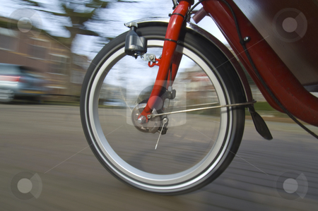 Spinning bicycle wheel stock photo, The spinning and vibrating wheel of a delivery bicycle on a suburban street by Corepics VOF