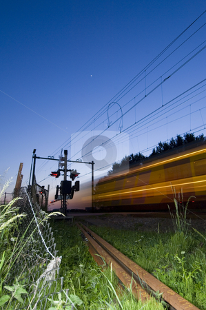 Railway intersection stock photo, A train passing a realway intersection at night by Corepics VOF