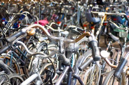 A sea of bicycles stock photo, Bicycles parked at the railway station; focus on the aluminium bike in the lower left by Corepics VOF