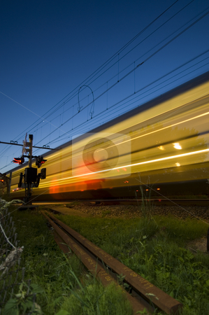Passing Train stock photo, A train at full speed passing a railway crossing at dusk by Corepics VOF