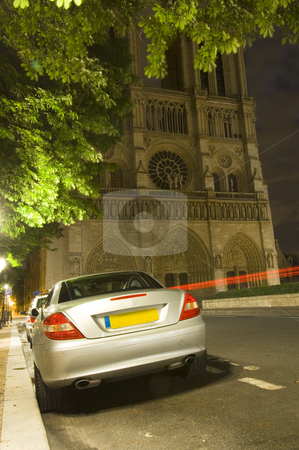 Illegal night parking stock photo, A sports car parked illeally at night in front of the Notre Dame Cathedral in Paris, in a spot reserved for taxis. The police car in front is issuing parking tickets while another car passes by by Corepics VOF