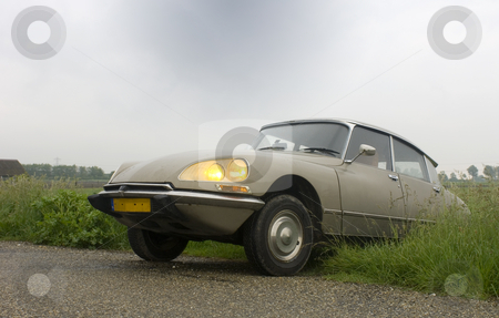 Classic Car on Vintage Road stock photo, A Vintage car parked on a country road in Zeeland, the Netherlands on a rainy day, with it's headlights on. by Corepics VOF