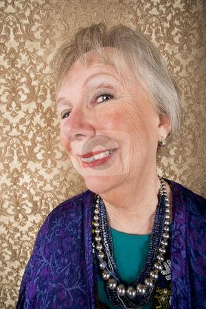 Smiling Senior Woman stock photo, Portrait of smiling senior woman in front of gold background by Scott Griessel