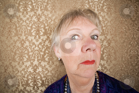 Snooty Senior Woman stock photo, Portrait of snooty senior woman in front of gold background by Scott Griessel