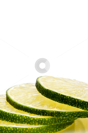 A vertical close-up of a stack of juicy fresh cut lime slices. stock photo, A vertical close-up of a stack of juicy fresh cut lime slices. by Vince Clements