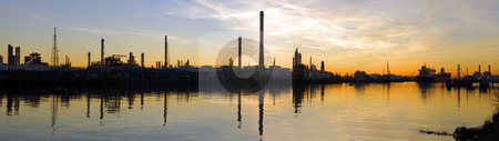 Oil Refinary at dusk stock photo, An oil refinary, located in the huge Rotterdam Harbor, at night, with the jetties and docks for the merchant ships. A huge oil tanker waiting to be reloaded. by Corepics VOF