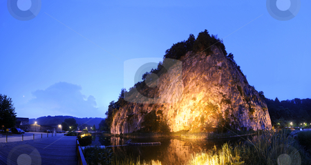 Illuminated Rock Formation stock photo, The massive rock formation, showing the geological lines during its forming in Durbuy, the smallest city in Europe at night by Corepics VOF