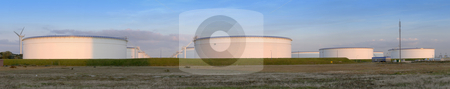 Oil tanks at sunset stock photo, Many oil tanks near a refinary in the Rotterdam Harbor Area basking in the evening light by Corepics VOF