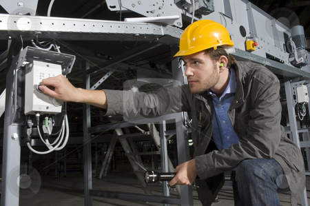 Turning on stock photo, An engineer, wearing the proper safety equipment, turning on a machine by twisting a knob by Corepics VOF