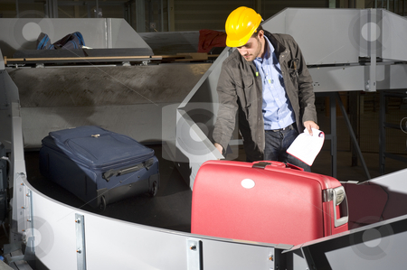 Luggage belt worker stock photo, A maintenance engineer inspecting a luggage handling conveyor belt at an airport by Corepics VOF