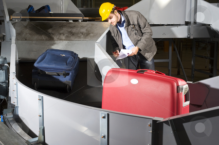 Checking luggage stock photo, An airport official checking luggage on a conveyor belt, wearing a hard hat and earplugs by Corepics VOF