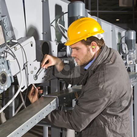 Maintenance engineer at work stock photo, A male maintenance engineer at work on an industrial appliance by Corepics VOF