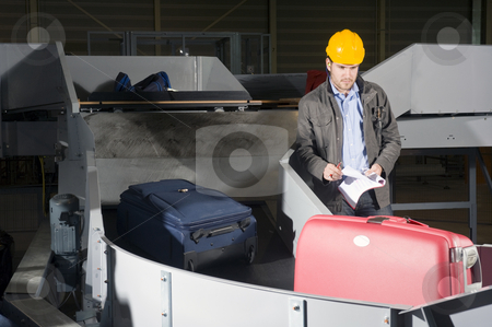 Luggage check at the Airport stock photo, A security staff manually checking luggage after the airport security check at the luggage conveyor belts by Corepics VOF