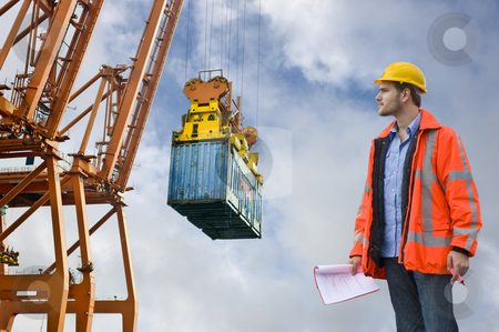 Customs Control inspecting at a commercial harbor stock photo, A Customs Control officer, checking the unloading of freight containers at an industrial harbor, wearing a hard hat and safety coat by Corepics VOF