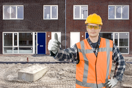 Satisfied construction worker stock photo, A construction worker giving his thumbs-up in front of a newly constructed residential building by Corepics VOF