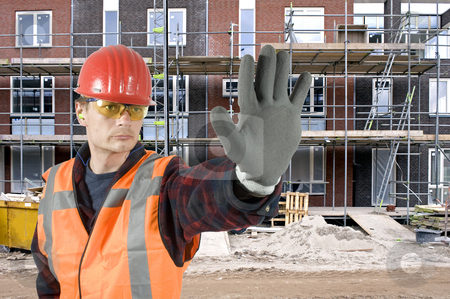Stop stock photo, A serious looking construction worker giving a stop signal with his hand in front of a huge residential building site by Corepics VOF