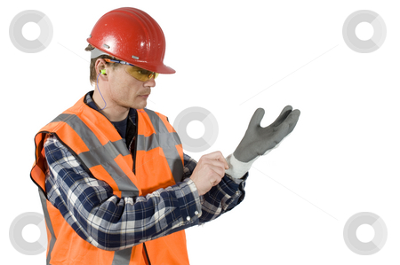 Putting on gloves stock photo, A worker, with a hard top, ear plugs and goggels putting on gloves for safety. Clipping Path included by Corepics VOF