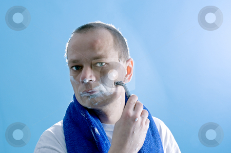 Shaving man stock photo, A middle aged man dressed in a white t-shirt, shaving himself by Corepics VOF