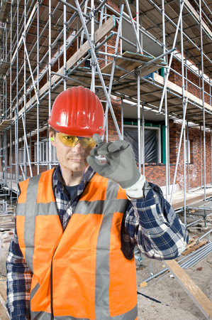 Saluting construction worker stock photo, A satisfied and confident construction worker touching his hard hat with his finger, greeting the customer by Corepics VOF