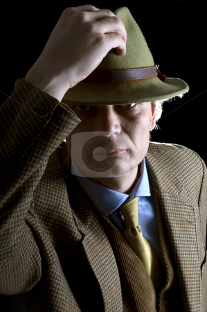 Retro Fashion stock photo, A man in his 30's dressed in rero fashion, lifting his hat and looking stern by Corepics VOF
