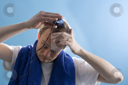 Self-service barber stock photo, A middle aged man dressed in a white t-shirt, shaving his own hair with a clipper by Corepics VOF
