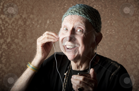 Elderly Hiptser Listening to Handheld Audio Device stock photo, Elderly Hiptser Listening to Small Handheld Audio Device by Scott Griessel