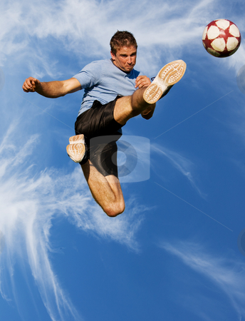 High kick stock photo, Athletic male high in the air kicking a soccer ball by Steve Mcsweeny