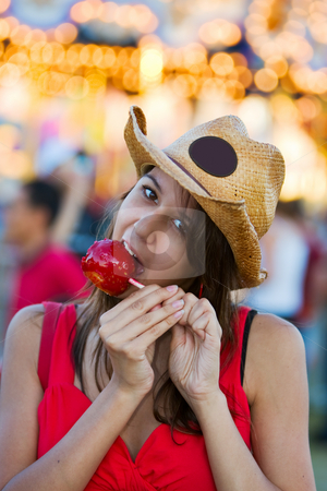 Candy apple snack stock photo, A pretty teen at the fair eating a candy apple by Steve Mcsweeny