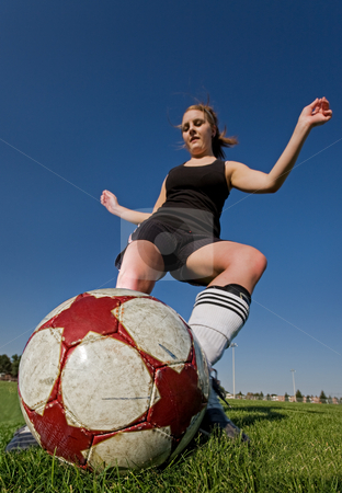 Female soccer kick stock photo, A female soccer player kicking the ball, main focus on the ball. by Steve Mcsweeny