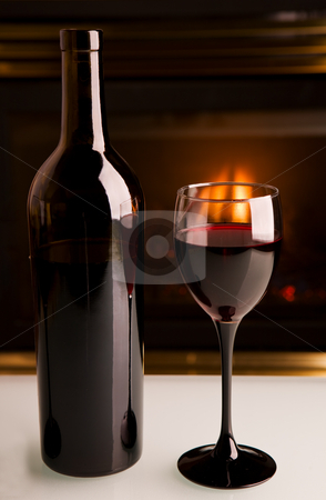 Table top wine stock photo, A bottle of red wine infront of a fireplace on a white table by Steve Mcsweeny