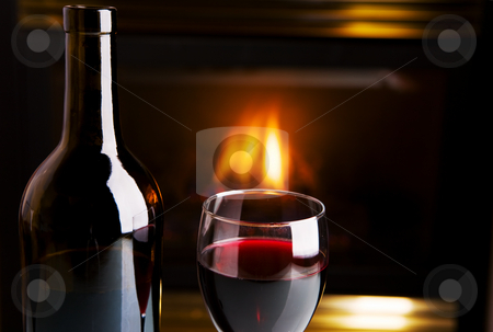 Wine and fire stock photo, A bottle of red wine and glass infront of a fireplace by Steve Mcsweeny